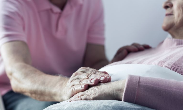 Elderly man comforting woman by holding hands in hospital