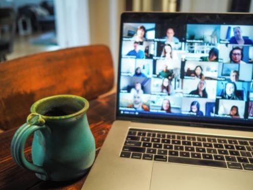 Coffee mug next to laptop showing online zoom meeting
