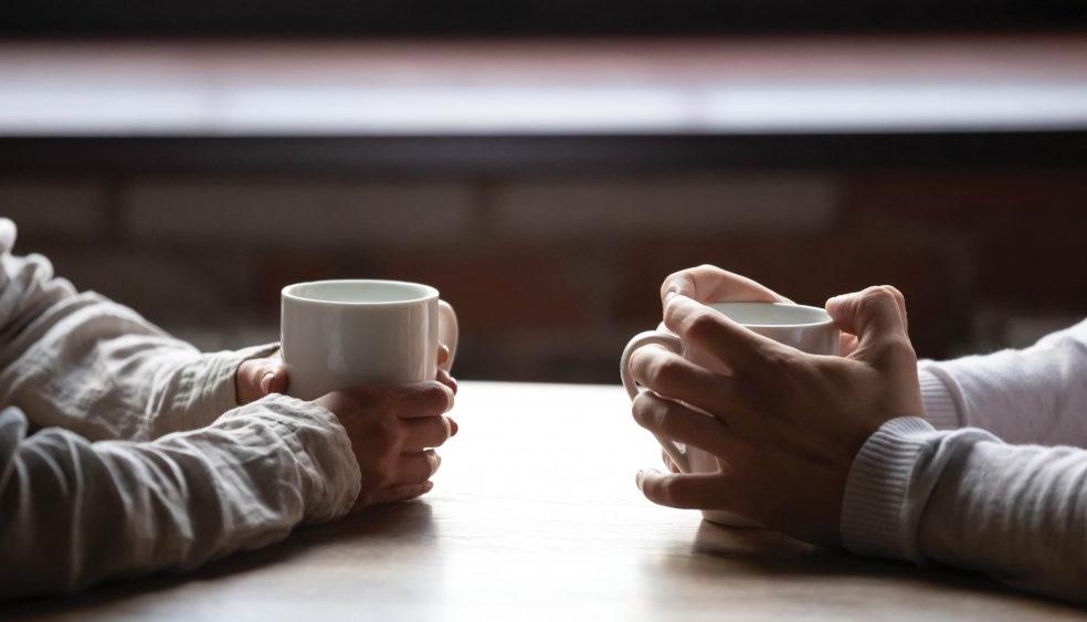 Hands clasping coffee mugs